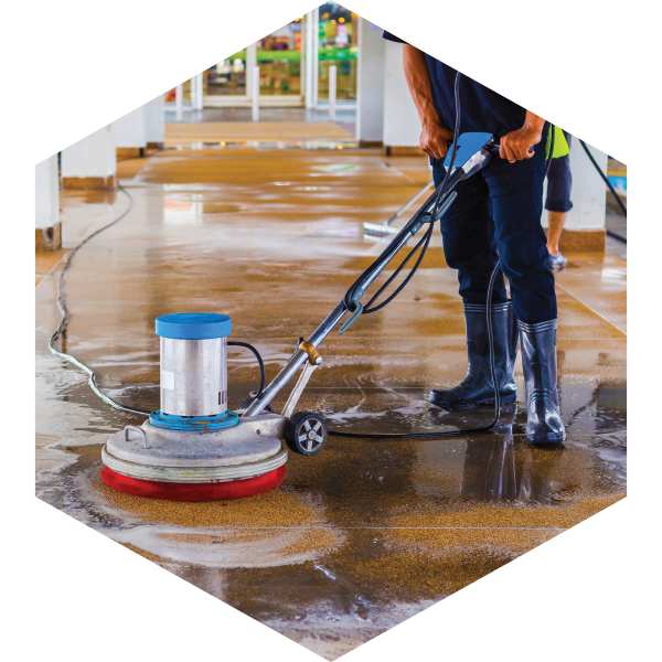 Phoro of a man cleaning the floor with a pressure washer surface cleaner